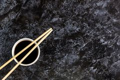 Japanese sushi chopsticks and soy sauce on black background. Top view with copyspace. Japanese sushi chopsticks and soy sauce on black stone background. Top view royalty free stock photo