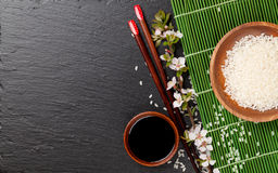 Japanese sushi chopsticks, soy sauce bowl, rice and sakura bloss Royalty Free Stock Images