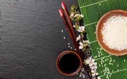 Japanese sushi chopsticks, soy sauce bowl, rice and sakura bloss Royalty Free Stock Images
