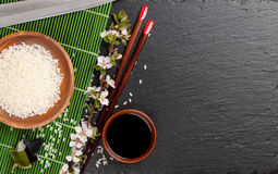 Japanese sushi chopsticks, soy sauce bowl, rice and sakura bloss Stock Photos