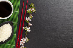 Japanese sushi chopsticks, soy sauce bowl, rice and sakura bloss Stock Photo