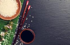 Japanese sushi chopsticks, soy sauce bowl, rice and sakura bloss Royalty Free Stock Photography