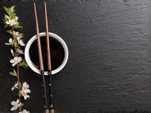 Japanese sushi chopsticks, soy sauce bowl and sakura blossom Royalty Free Stock Photography