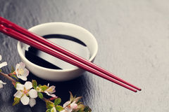 Japanese sushi chopsticks, soy sauce bowl and sakura blossom Royalty Free Stock Photos