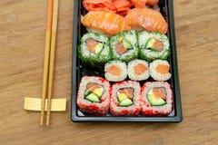 Japanese sushi and chopsticks on the wooden background Stock Image