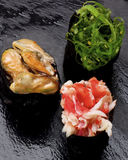 Japanese Sushi Gunkan. Various Japanese Sushi Gunkan Rolled Up in Nigiri with Seaweed, Shrimps and Mussels in Sauce closeup on Wet Slate background. Focus on Stock Image