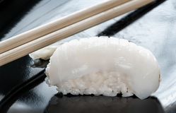 Japanese sushi made of rice and sea bass with chopsticks on a black plate. The horizontal frame royalty free stock image