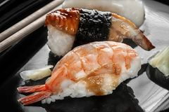 Japanese sushi made of rice and sea bass, shrimp and smoked eel with chopsticks on a black plate. The horizontal frame stock photography