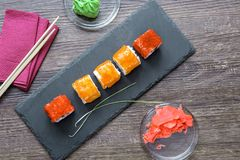Japanese sushi rice and sea bass, shrimp and smoked eel with caviar of flying fish with Philadelphia cheese, chopsticks. On a black plate of shale stock images