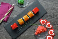 Japanese sushi rice and sea bass, shrimp and smoked eel with caviar of flying fish with Philadelphia cheese, chopsticks. On a black plate of shale royalty free stock photography