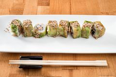 Japanese sushi roll green dragon with eel and avocado with ginger on a white plate. isolated. close up royalty free stock photography