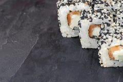 Japanese sushi roll philadelphia on black stone. Stock Images