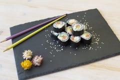 Japanese sushi rolls. With chopsticks on a black slate Stock Photos