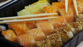 Japanese Sushi Rolls with Chopsticks Rotates. Close-up. Variety of types sushi with Philadelphia cheese, sesame, red caviar, salmon fillets. Set of delicious stock video