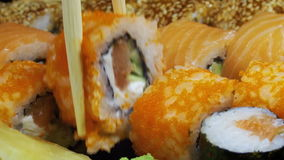 Japanese Sushi Rolls with Chopsticks Rotates. Close-up. Variety of types sushi with Philadelphia cheese, sesame, red caviar, salmon fillets. Set of delicious stock footage