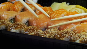 Japanese Sushi Rolls with Chopsticks Rotates. Close-up. Variety of types sushi with Philadelphia cheese, sesame, red caviar, salmon fillets. Set of delicious stock video footage