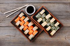 Japanese sushi rolls, chopsticks and sauce bowls stock photography