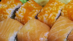 Japanese Sushi Rolls close-up is Moving. Variety of types sushi with Philadelphia cheese, sesame, red caviar, salmon fillets. Macro shot of sushi. Sushi plate stock footage