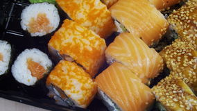 Japanese Sushi Rolls Close-up Rotates. Variety of types sushi with Philadelphia cheese, sesame, red caviar, salmon fillets. Macro shot of sushi plate. Set of stock video footage