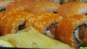 Japanese sushi rolls close-up rotates. Variety of types sushi with Philadelphia cheese, sesame, red caviar, salmon fillets. Macro shot of sushi plate. Set of stock video