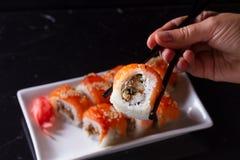 Japanese sushi dish. Japanese sushi rolls dish with hand holding one piece in chopsticks Royalty Free Stock Photo