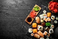 Japanese sushi rolls with salmon, avocado and shrimp. On black rustic background royalty free stock photo