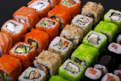 Japanese sushi rolls. In the shape of a line on black background top view Stock Photos