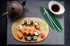 Japanese sushi rolls, soy sauce, ginger and chopsticks on dark background. Top view. Flat lay. Stock Image