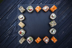 Japanese sushi on a rustic dark background. Japanese sushi on a black stone plate background Royalty Free Stock Photography