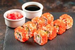 Japanese sushi on a rustic dark background. Japanese sushi rolls served on stone slate on dark background. Sushi rolls, maki, pickled ginger and soy sauce. Sushi royalty free stock photos