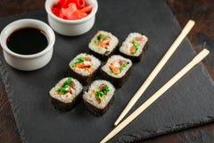 Japanese sushi on a rustic dark background. Japanese sushi rolls served on stone slate on dark background. Sushi rolls, maki, pickled ginger and soy sauce. Sushi stock photos