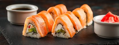 Japanese sushi on a rustic dark background. Japanese sushi rolls served on stone slate on dark background. Sushi rolls, maki, pickled ginger and soy sauce. Sushi stock photo