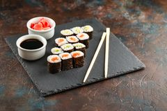 Japanese sushi on a rustic dark background. Japanese sushi rolls served on stone slate on dark background. Sushi rolls, maki, pickled ginger and soy sauce. Space stock images