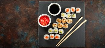 Japanese sushi on a rustic dark background. Japanese sushi rolls served on stone slate on dark background. Sushi rolls, maki, pickled ginger and soy sauce. Space royalty free stock photos