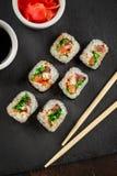 Japanese sushi on a rustic dark background. Japanese sushi rolls served on stone slate on dark background. Sushi rolls, maki, pickled ginger and soy sauce. Top stock photo