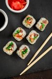 Japanese sushi on a rustic dark background. Japanese sushi rolls served on stone slate on dark background. Sushi rolls, maki, pickled ginger and soy sauce. Top royalty free stock photography