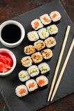 Japanese sushi on a rustic dark background. Japanese sushi rolls served on stone slate on dark background. Sushi rolls, maki, pickled ginger and soy sauce. View stock photography