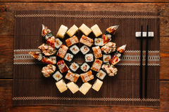 Japanese sushi set assorted, flat lay. Food art. Japanese assorted tasty fresh sushi set served on brown straw mat, flat lay. Food art, mosaic of delicious Stock Photography
