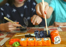 Japanese sushi set with kids hands. Teen siblings boy and girl kids with sushi rolls avocado and salmon close up smiling photo Stock Images