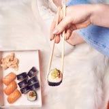 Japanese sushi set nigiri and sushi rolls served with wasabi and ginger, girls hands holding sushi royalty free stock images