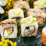 Japanese Sushi Set. Various Maki Sushi Roll on Black Stone. Japanese Cuisine and Natural Flower Concept Stock Photography