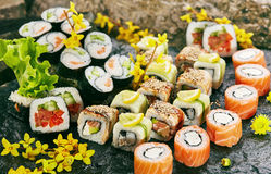Japanese Sushi Set. Various Maki Sushi Roll on Black Stone. Japanese Cuisine and Natural Flower Concept Stock Photos