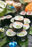 Japanese Sushi Set. Various Maki Sushi Roll on Black Stone. Japanese Cuisine and Natural Flower Concept Royalty Free Stock Photography