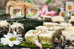 Japanese Sushi Set. Various Maki Sushi Roll on Black Stone. Japanese Cuisine and Natural Flower Concept Stock Photo