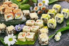 Japanese Sushi Set. Various Maki Sushi Roll on Black Stone. Japanese Cuisine and Natural Flower Concept Royalty Free Stock Image