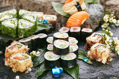 Japanese Sushi Set. Various Maki Sushi Roll on Black Stone. Japanese Cuisine and Natural Flower Concept Royalty Free Stock Photo