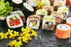 Japanese Sushi Set. Various Maki Sushi Roll on Black Stone. Japanese Cuisine and Natural Flower Concept Royalty Free Stock Photos