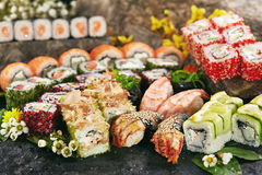 Japanese Sushi Set. Various Maki Sushi Roll and Nigiri Sushi. Japanese Cuisine and Natural Flower Concept Stock Image