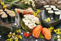 Japanese Sushi Set. Various Maki Sushi Roll and Nigiri Sushi. Japanese Cuisine and Natural Flower Concept Stock Photos