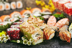 Japanese Sushi Set. Various Maki Sushi Roll and Nigiri Sushi. Japanese Cuisine and Natural Flower Concept Stock Images